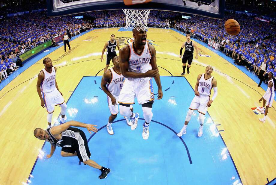 The Thunder's Serge Ibaka is sky high after blocking the shot of the Spurs' Tony Parker, left, in the second half. Ibaka, who missed the series' first two games, had three more blocks, 15 points and seven rebounds. Photo: Ronald Martinez, Staff / 2014 Getty Images