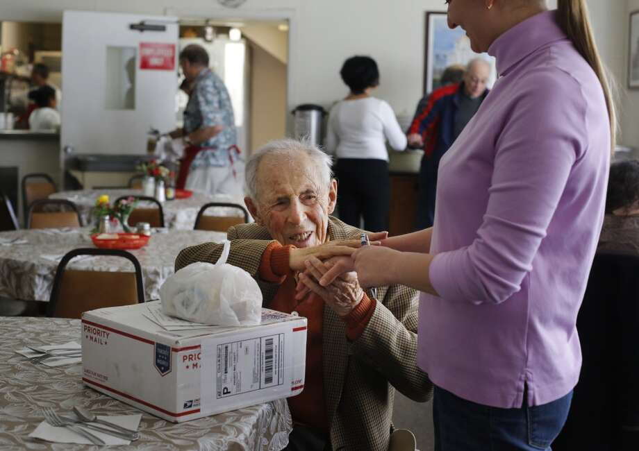 Julius Mansbach, 100, thanks Maria Ksenzova after she delivered the latest shipment of stamps, from Chronicle readers, before lunch at the Russian American Community Services center on Wednesday 21, 2014 in San Francisco, Calif. Photo: Mike Kepka , The Chronicle