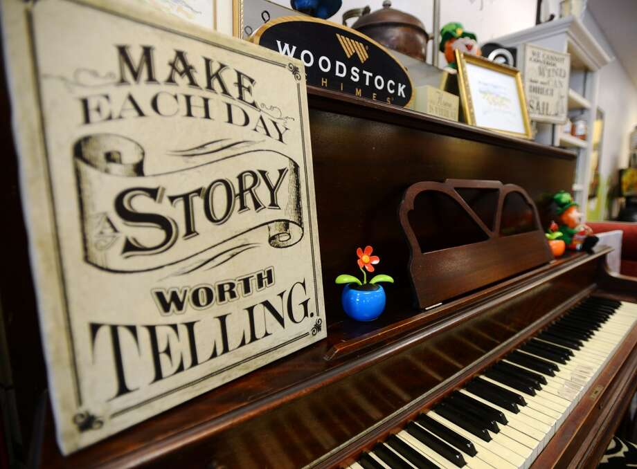 An upright piano -- out of tune but functional, says Herb Kreutzer -- at Kizmet Studio is adorned with signs and plastic potted plants. Kizmet Studio in Groves has been at its current location for a little over a year now, and was at its former location on Lincoln Avenue for three years. The coffee shop and cafe also hosts live music and offers art lessons in a large back room. Photo taken Monday 5/12/14 Jake Daniels/@JakeD_in_SETX