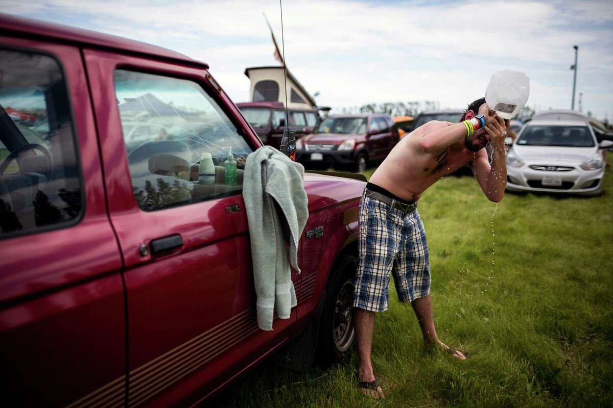 Camper Carey Rose freshens up with a head shower of distilled water and soap on the third and final day of the annual Sasquatch music festival Sunday, May 25, 2014, in George, Wash.