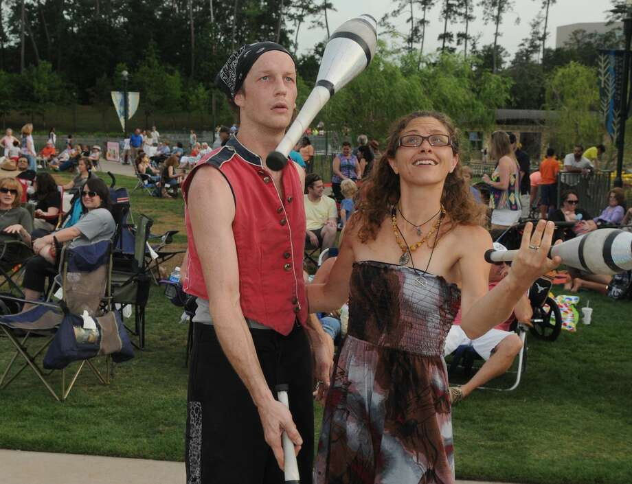 """Mr. Cirque"" (Noah Maudlin of Kemah) and his wife, Lynsey, team up to entertain the crowd during the Memorial Day Weekend Celebration at Town Green Park in The Woodlands on May 25th. Photo: Jerry Baker, For The Chronicle"