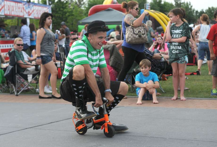 """Roly the Clown"" (Roly Gutierrez of Katy) entertains the crowd during the Memorial Day Weekend Celebration at Town Green Park in The Woodlands on May 25th. Photo: Jerry Baker, For The Chronicle"