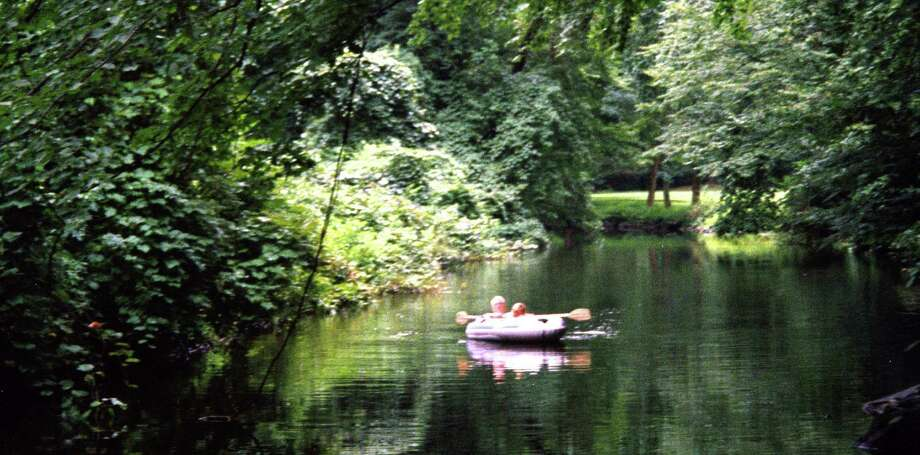 Actor-philanthropist Paul Newman and grandson enjoy a quiet paddle on a wooded stretch of the Aspetuck River near his former home, now part of the Newman-Poses Preserve. Photo: Aspetuck Land Trust / Westport News