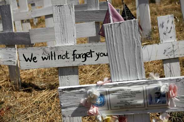 Pictures of fallen soldiers and personal messages are seen on crosses at the Crosses of Lafayette war memorial which covers a hillside next to the Lafayette BART station in Lafayette, CA, Wednesday May 21, 2014.