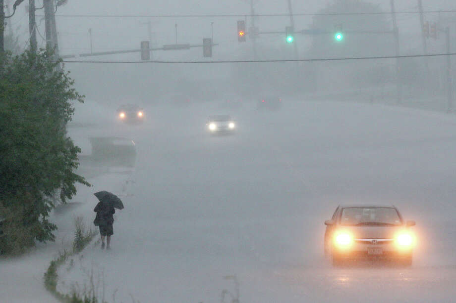 A pedestrian walks along Potranco Road as heavy rains move through the area, Monday, May 26, 2014. The National Weather Service has issued flash flood warnings for the area. Photo: JERRY LARA, San Antonio Express-News / © 2014 San Antonio Express-News