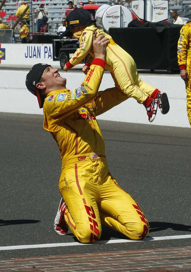 Daddy's the champ: Traditionally, the winner of the Indy 500 throws milk on himself, but this year's winner, Ryan Hunter-Reay, briefly substituted a child. Later, he did in fact pour milk over his head. Photo: Tom Strattman, Associated Press