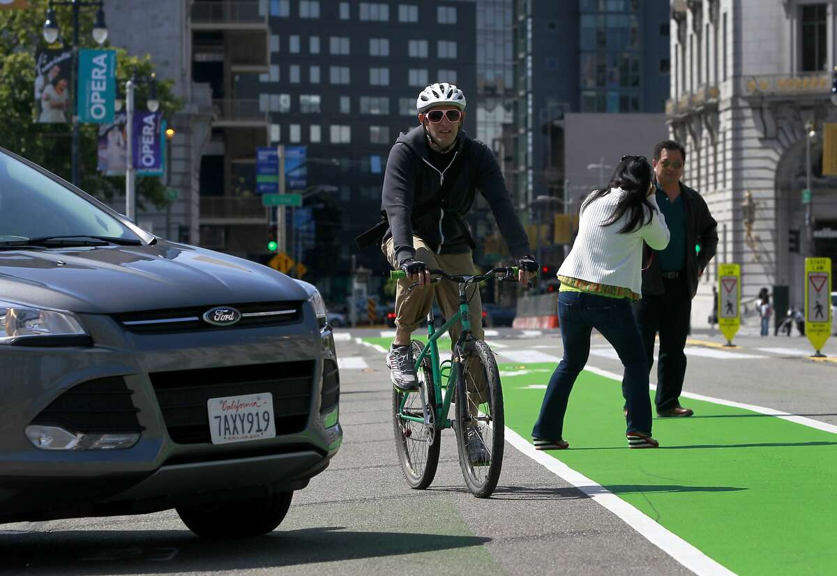 A bicyclist riding north on Polk Street has to steer through an obstacle course which includes a car backing into a parking space and tourists snapping photos in the middle of a new bike lane in front of City Hall in San Francisco, Calif. on Saturday, May 24, 2014.