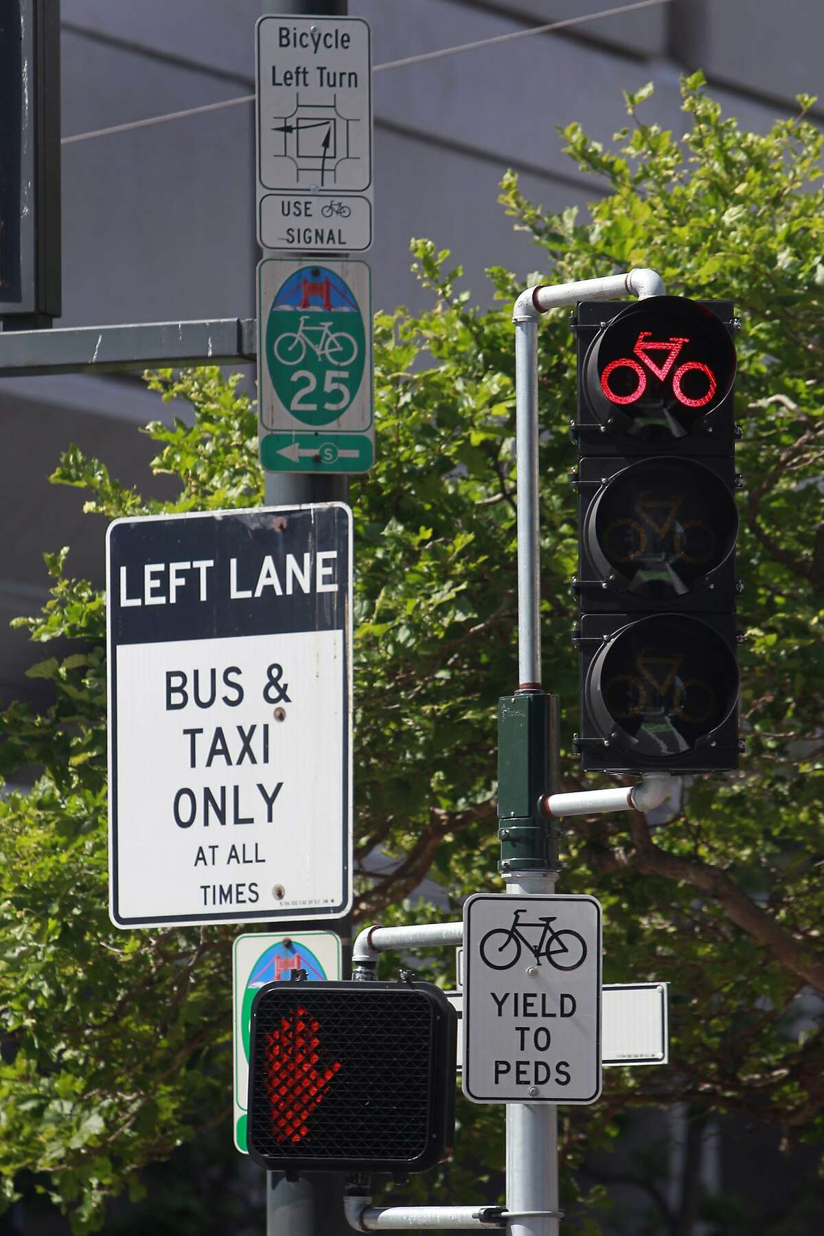 A collection of traffic signs assist bicyclists through a maze of complex maneuvers at Polk and Market streets in San Francisco, Calif. on Saturday, May 24, 2014.