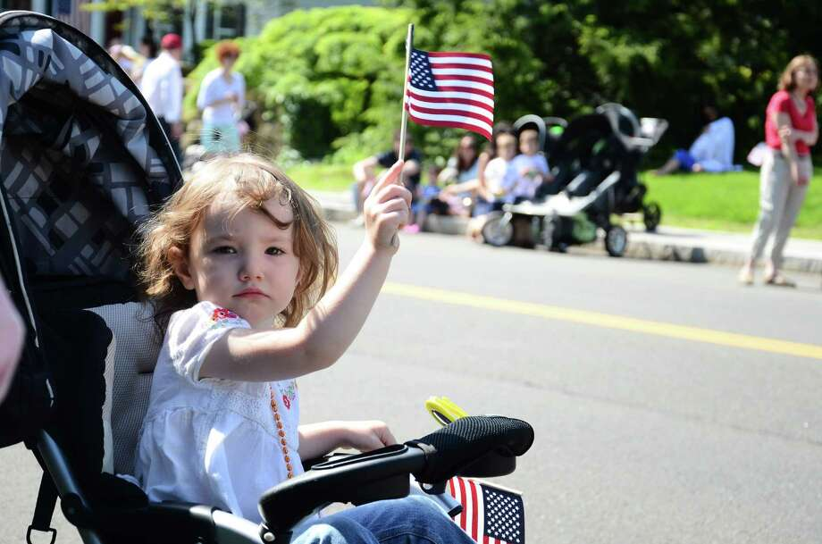 Two-year-old Kelsey Guynn waves a flag to parade marchers during the 2014 Memorial Day Parade in New Canaan, Conn., Monday, May 26, 2014. Photo: Nelson Oliveira / New Canaan News