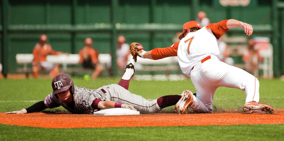Texas A&M's Scott Arthur (14) reaches for second after trying to steal third, while UT's Jordan Etier (7)  on April 29, 2012 at Disch-Faulk Field.
