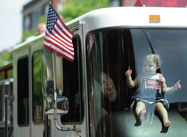 Michelle Dimauro, of Danbury, laughs as her daughter, Addison Dimauro, 9 months, moves along to the music while riding in a firetruck during the Memorial Day parade on Main Street in Danbury, Conn. Monday, May 26, 2014.  The parade began at Rose Street and Main Street, finishing at Rogers Park, where skydivers dropped onto the field at Rogers Park Middle School. The parade was followed by