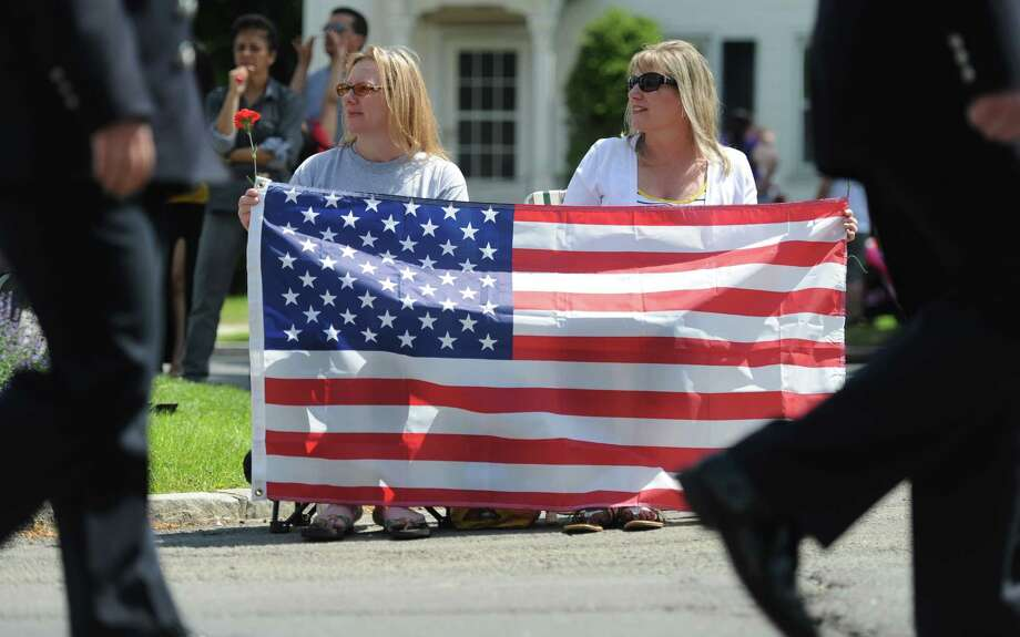 Danbury residents Melinda McKague, left, and Debbie LoStocco watch the the Memorial Day parade on Main Street in Danbury, Conn. Monday, May 26, 2014.  The parade began at Rose Street and Main Street, finishing at Rogers Park, where skydivers dropped onto the field at Rogers Park Middle School. The parade was followed by a memorial service at the Rogers Park Rose Memorial Garden. Photo: Tyler Sizemore / The News-Times
