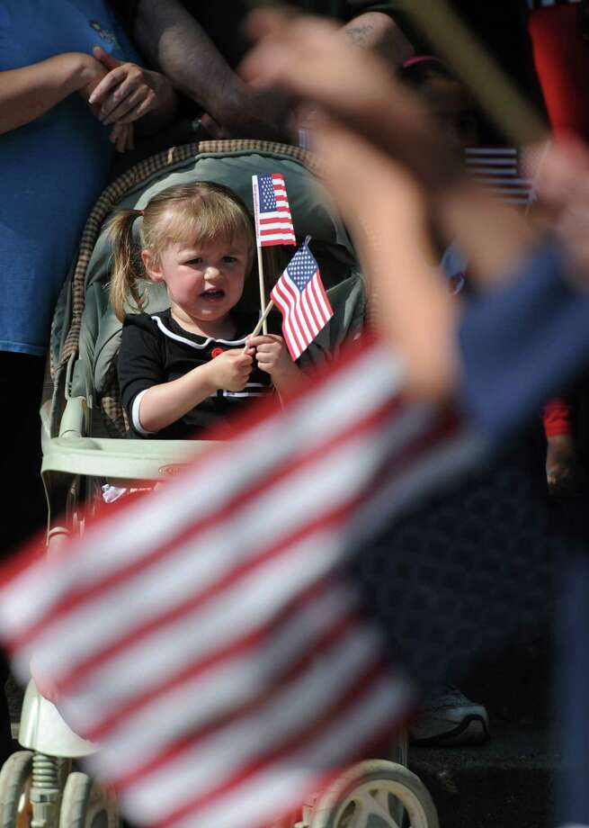Madilynn Rose, 2, of Danbury, waves flags as the Memorial Day parade passes by on Main Street in Danbury, Conn. Monday, May 26, 2014.  The parade began at Rose Street and Main Street, finishing at Rogers Park, where skydivers dropped onto the field at Rogers Park Middle School. The parade was followed by a memorial service at the Rogers Park Rose Memorial Garden. Photo: Tyler Sizemore / The News-Times