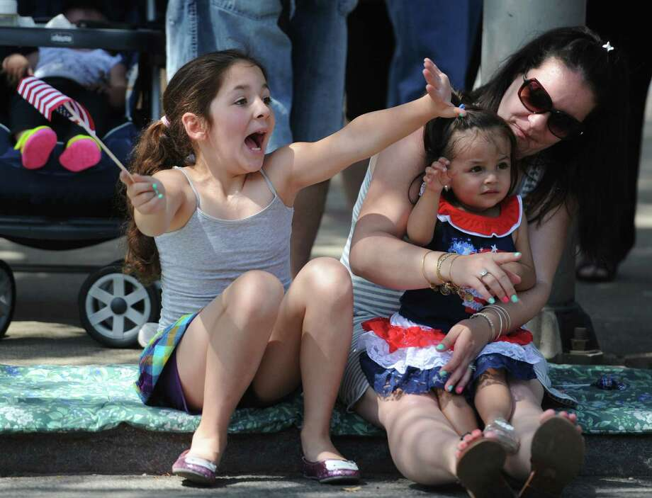 Sofia Siharaj, 8, enthusiastically waves while sitting next to her mother, Marissa Siharaj, and sister, Lillianna Siharaj, 1, of Danbury, at the Memorial Day parade on Main Street in Danbury, Conn. Monday, May 26, 2014.  The parade began at Rose Street and Main Street, finishing at Rogers Park, where skydivers dropped onto the field at Rogers Park Middle School. The parade was followed by a memorial service at the Rogers Park Rose Memorial Garden. Photo: Tyler Sizemore / The News-Times