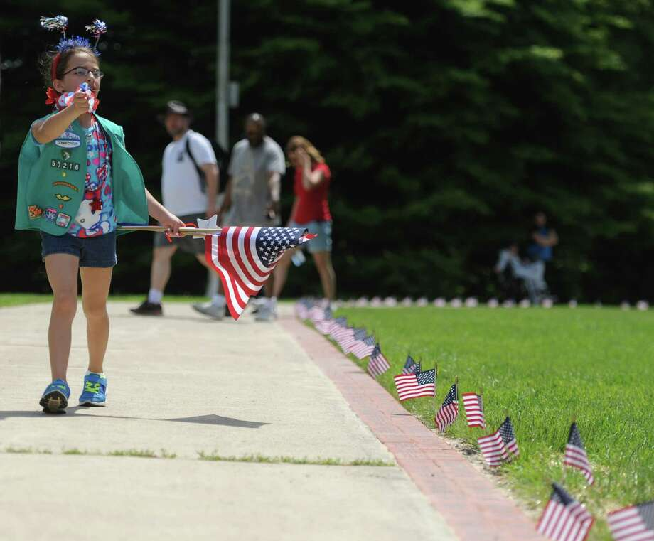 Savannah Hadda, 9, of Danbury, walks along the sidewalk outside the Danbury War Memorial during the Memorial Day parade on Main Street in Danbury, Conn. Monday, May 26, 2014.  The parade began at Rose Street and Main Street, finishing at Rogers Park, where skydivers dropped onto the field at Rogers Park Middle School. The parade was followed by a memorial service at the Rogers Park Rose Memorial Garden. Photo: Tyler Sizemore / The News-Times