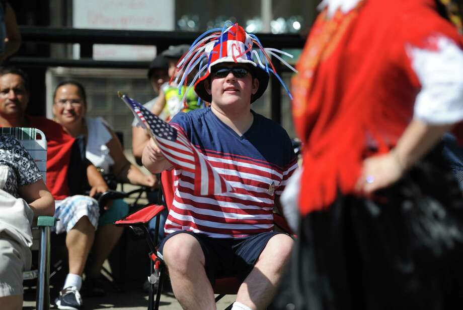 Michael Vitti, of Brookfield, waves a flag during the Memorial Day parade on Main Street in Danbury, Conn. Monday, May 26, 2014.  The parade began at Rose Street and Main Street, finishing at Rogers Park, where skydivers dropped onto the field at Rogers Park Middle School. The parade was followed by a memorial service at the Rogers Park Rose Memorial Garden. Photo: Tyler Sizemore / The News-Times