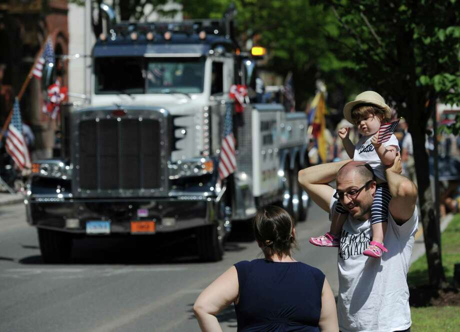 Parents Anthony and Angela Mills, of Danbury, watch the parade with their daughter, Darby Mills, 20 months, at the Memorial Day parade on Main Street in Danbury, Conn. Monday, May 26, 2014.  The parade began at Rose Street and Main Street, finishing at Rogers Park, where skydivers dropped onto the field at Rogers Park Middle School. The parade was followed by a memorial service at the Rogers Park Rose Memorial Garden. Photo: Tyler Sizemore / The News-Times