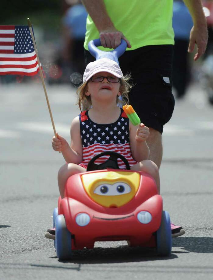 Riley Burke, 3, of Danbury, waves a flag during the Memorial Day parade on Main Street in Danbury, Conn. Monday, May 26, 2014.  The parade began at Rose Street and Main Street, finishing at Rogers Park, where skydivers dropped onto the field at Rogers Park Middle School. The parade was followed by a memorial service at the Rogers Park Rose Memorial Garden. Photo: Tyler Sizemore / The News-Times