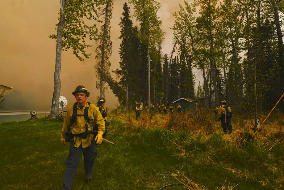 Serious decisions in Funny River: Firefighters assess whether they can protect a property from a wildfire in the Funny River community of Soldotna, 