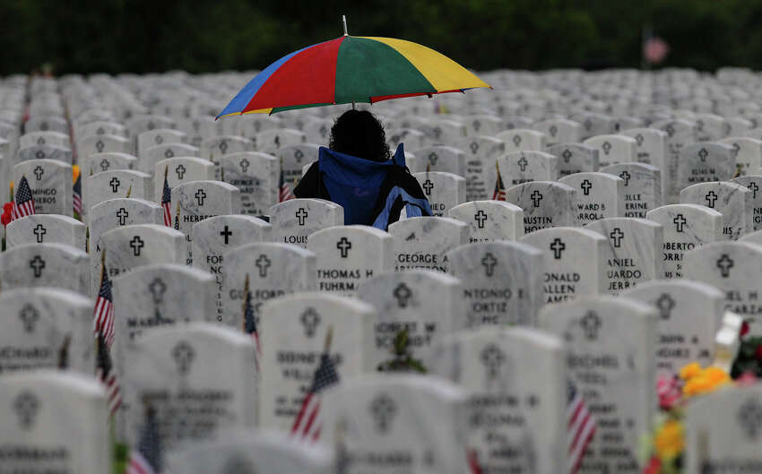 Laurie Carranza sits under an umbrella Memorial Day Monday May 26, 2014 at Ft. Sam Houston National Cemetery. Carranza was visiting the graves of father Angel Carranza, a veteran of the Korean War and her mother, Rosa P. Carranza. A Memorial Day ceremony was also held at the cemetery.