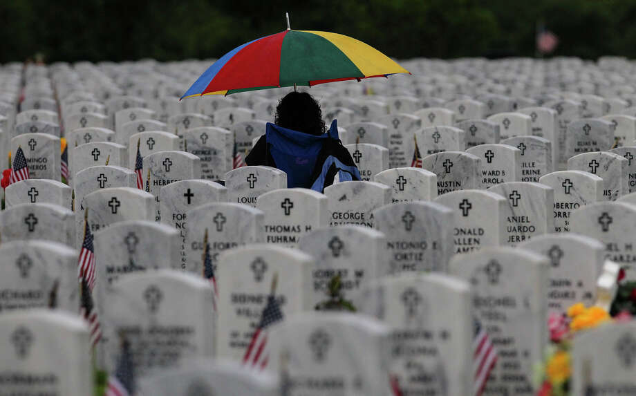 Laurie Carranza sits under an umbrella Memorial Day Monday May 26, 2014 at Ft. Sam Houston National Cemetery. Carranza was visiting the graves of father Angel Carranza, a veteran of the Korean War and her mother, Rosa P. Carranza. A Memorial Day ceremony was also held at the cemetery. Photo: JOHN DAVENPORT, San Antonio Express-News / ©San Antonio Express-News/John Davenport
