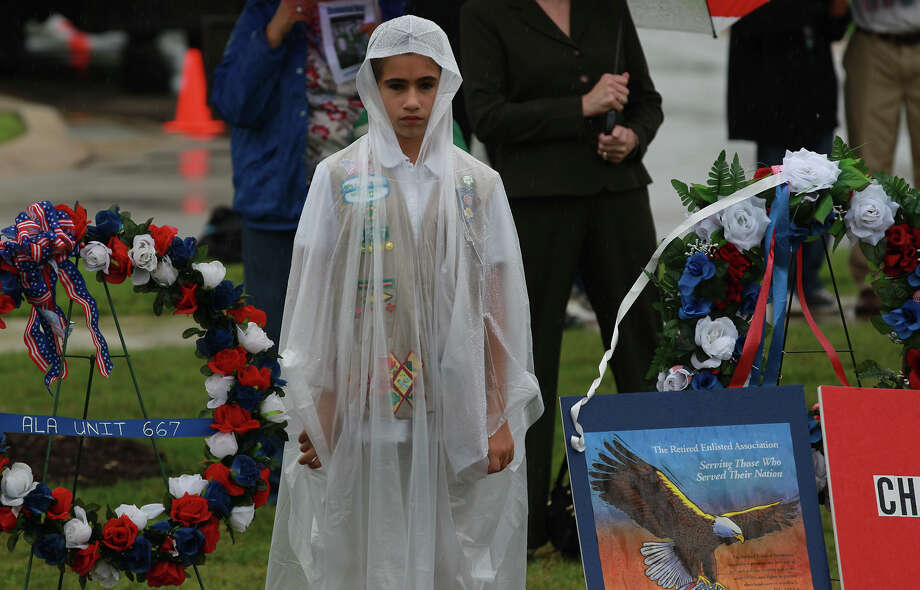 Bernadette Deremiah, 12, stands draped in plastic by while drizzle falls Monday May 26, 2014 during a Memorial Day Ceremony at Ft. Sam Houston National Cemetery. Photo: JOHN DAVENPORT, San Antonio Express-News / ©San Antonio Express-News/John Davenport