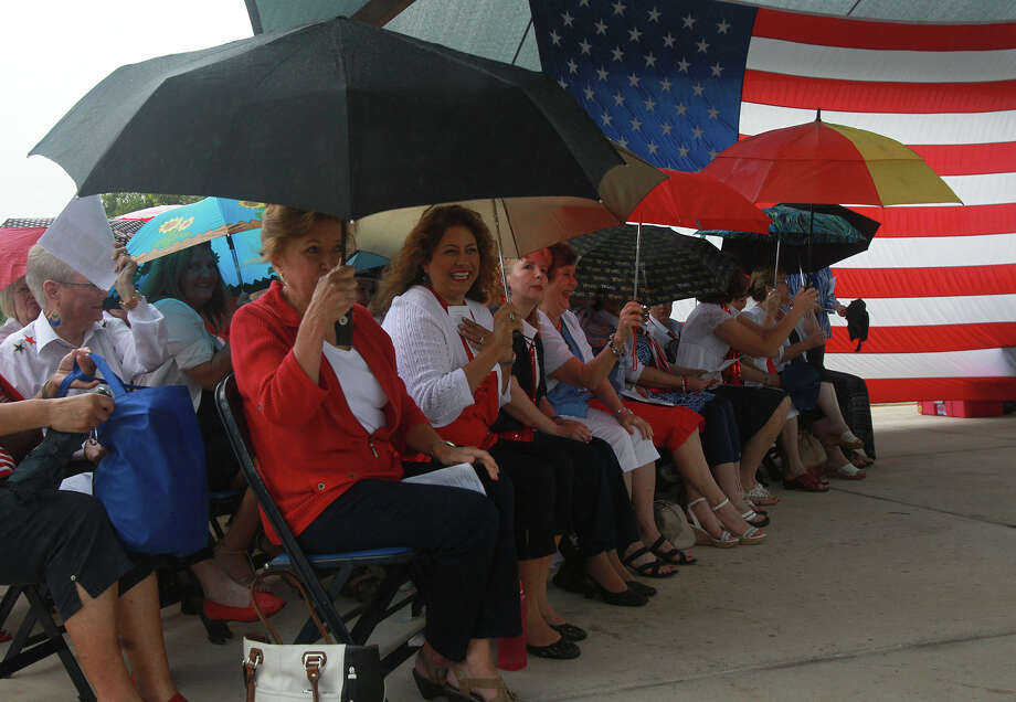 Ladies with the Alamo Metro Chorus of Sweet Adelines International take cover as rain moves in Monday May 26, 2014 during a Memorial Day Ceremony at Ft. Sam Houston National Cemetery. Photo: JOHN DAVENPORT, San Antonio Express-News / ©San Antonio Express-News/John Davenport