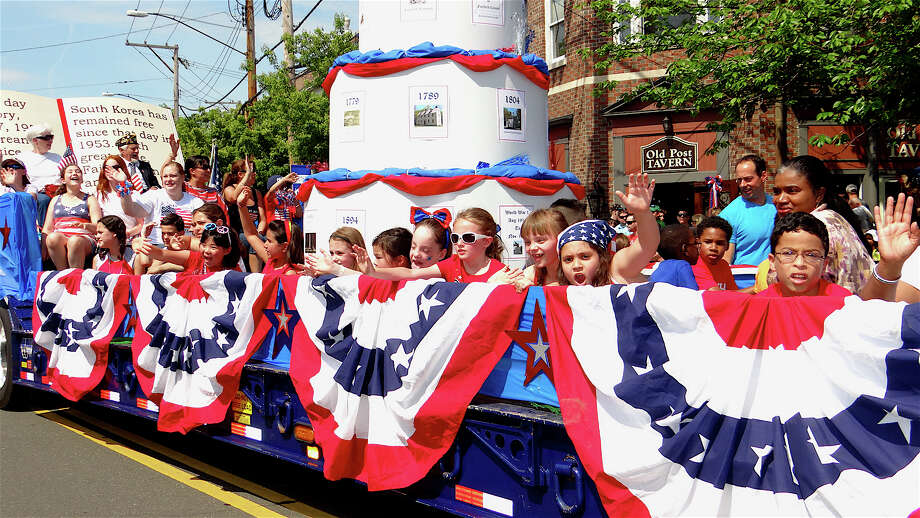 McKinley Elementary School students wave from their float on Post Road during Monday's Memorial Day parade. Photo: Mike Lauterborn / Fairfield Citizen