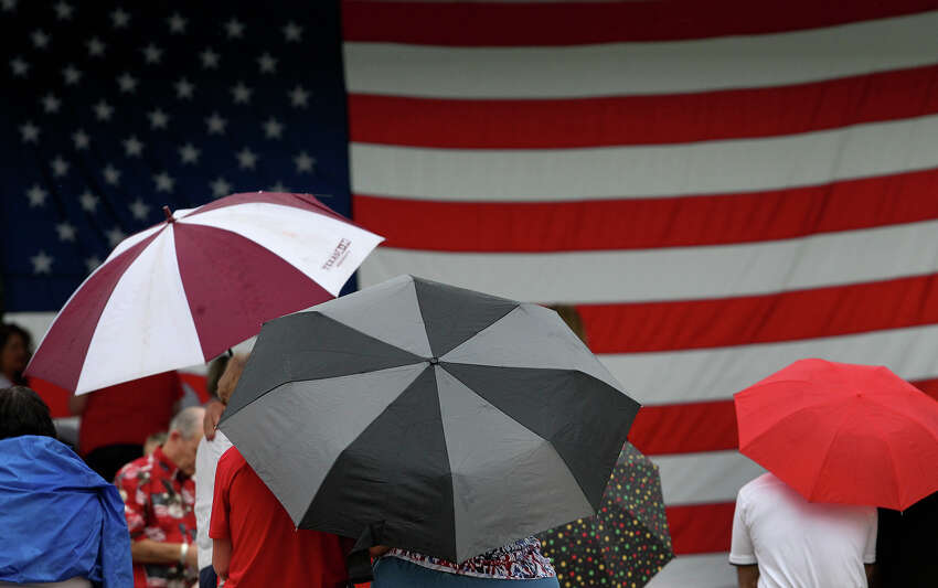 People attending a Memorial Day ceremony Monday May 26, 2014 at Ft. Sam Houston National Cemetery huddle under umbrellas as drizzle and scattered showers sweep through the San Antonio area.