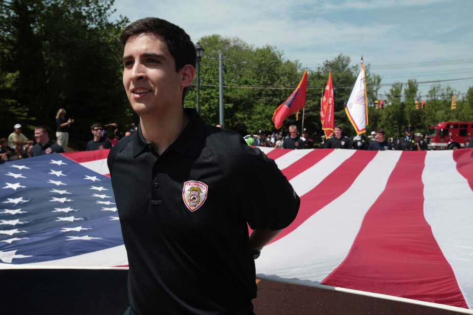 Junior firefighter David Gomez holds the flag with other members of the Trumbull fire department during the Trumbull Memorial Day Parade on Monday, May 26, 2014. Photo: BK Angeletti, B.K. Angeletti / Connecticut Post freelance B.K. Angeletti