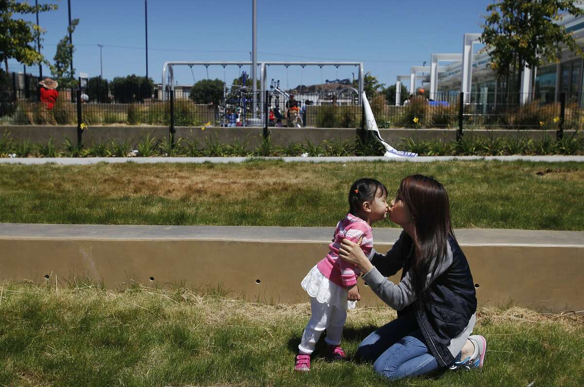 Xiuling Zhao, 27, kisses her daughter Queenie Huang, 2, as they pose for a portrait May 26, 2014 at the Palega Rec Center, near their home in San Francisco, Calif.
