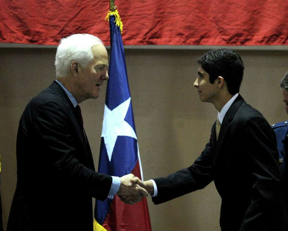 Jonathan Castaneda of San Antonio shakes hands with U.S. Sen. John Cornyn during the 8th annual send-off ceremony for Texas students who will be attending the nation's military service academies. Castaneda will attend the Naval Academy. The event took place at Freeman Coliseum on Memorial Day, May 26, 2014. Major General John F. Nichols gave the keynote address. Medal of Honor recipient Major General Patrick Brady also participated in the event. Photo: Billy Calzada, San Antonio Express-News / San Antonio Express-News