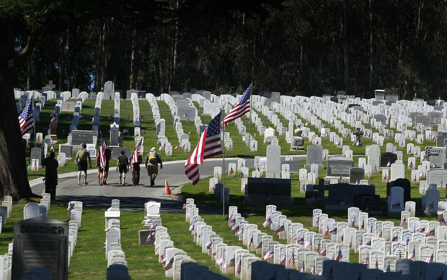 Visitors walk with U.S. flags at the National Cemetery of The Presidio during the Memorial Day Ceremony in San Francisco, Calif. on Monday, May 26, 2014. Photo: Paul Chinn, The Chronicle