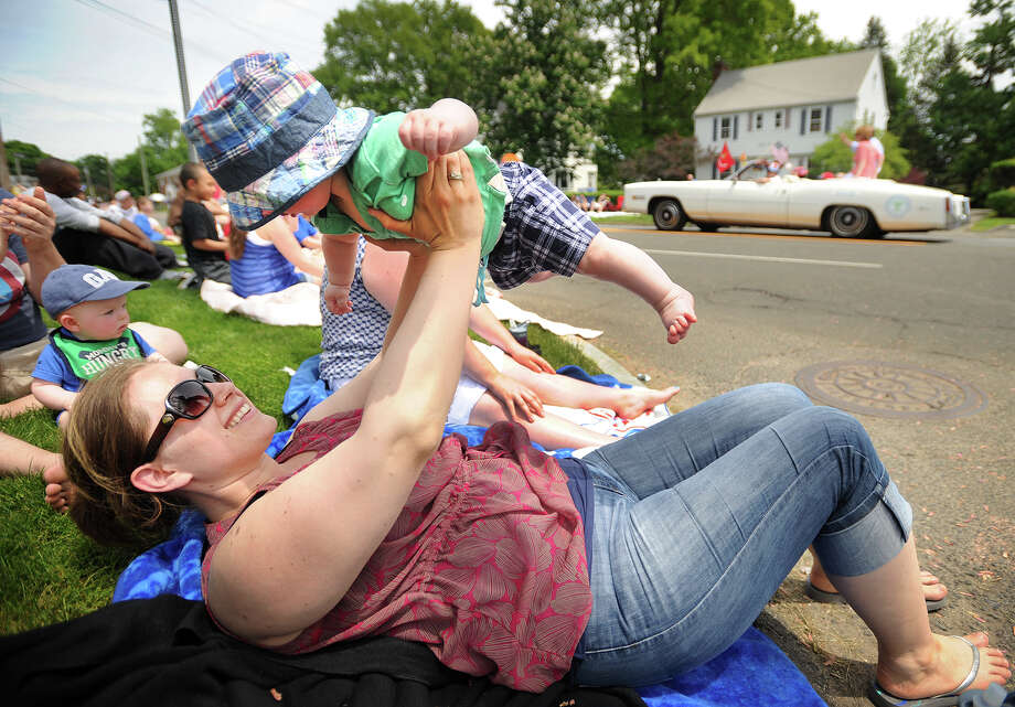 Visiting family for the holiday weekend, Kirin White, of Cheshire, plays with her son Brennan, 6 months, while watching the Memorial Day Parade on Main Street in Stratford, Conn. on Monday, May 26, 2014. Photo: Brian A. Pounds / Connecticut Post