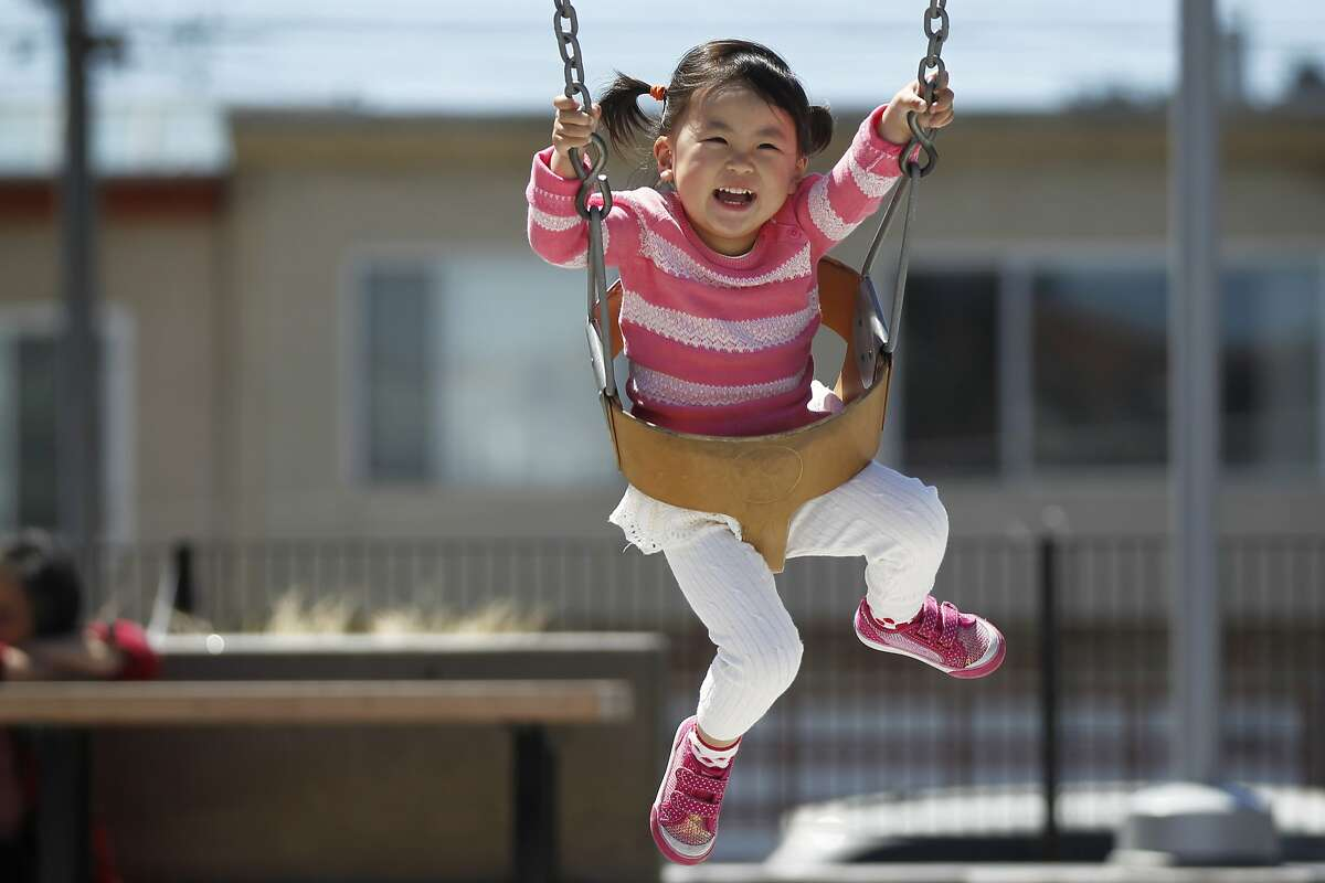 Queenie Huang, 2, laughs as she's pushed on the swing by her mother Xiuling Zhao, 27, May 26, 2014 at the Palega Rec Center, near their home in San Francisco, Calif.