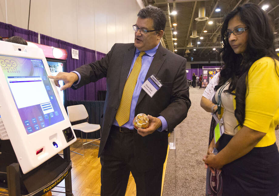 Chuck Olson, owner and operator of CNC Vending LLC, demos his touchscreen product to Angie Martinez of Benefits Solutions at a recent symposium on human resource issues. Photo: Billy Smith II / Houston Chronicle
