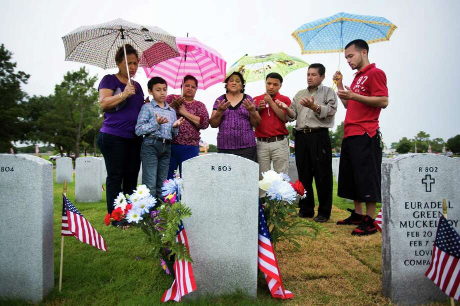 (left to right) Gloria Sorto, Anthony Hernandez, Matilda Rodas, Carmen Pacheco, Ricardo Lopez, Carlos Sorto and William Sorto, pray at the grave of John Carlos Sorto at the Houston National Cemetery during Memorial Day. Sorto was a U.S Army Sergeant who perished in Arizona after retuning from his third combat tour in Iraq. Monday, May 26, 2014, in Houston. Photo: Marie D. De Jesus, Houston Chronicle / © 2014 Houston Chronicle