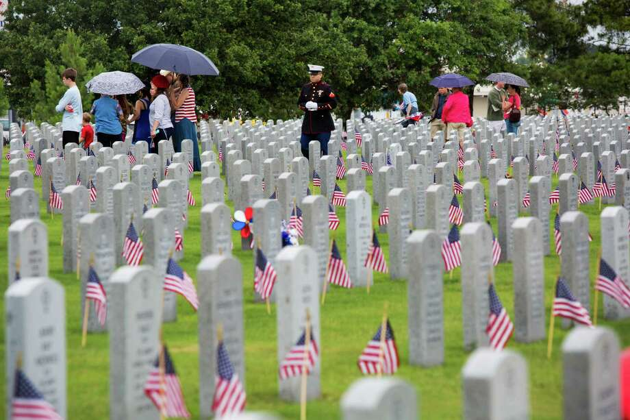 Families brave the rain and visit the graves of their U.S. serviceman and women on Memorial Day at the Houston National Cemetery, Monday, May 26, 2014, in Houston. Photo: Marie D. De Jesus, Houston Chronicle / © 2014 Houston Chronicle