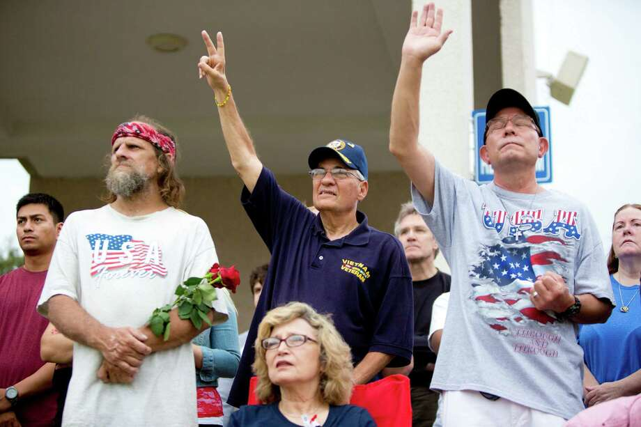 Michael Levine, center, and Ernest Barajas, right, get emotional during a patriotic hymn sang at the Memorial Day Service at the Houston National Cemetery, Monday, May 26, 2014, in Houston. Photo: Marie D. De Jesus, Houston Chronicle / © 2014 Houston Chronicle