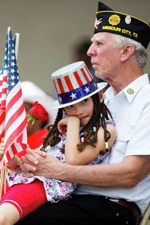 Esther Hord, 7, and her grandfather Larry Hord a Vietnam veteran, visit the Houston National Cemetery to honor the deceased United States servicemen and women during Memorial Day,  Monday, May 26, 2014, in Houston. Photo: Marie D. De Jesus, Houston Chronicle / © 2014 Houston Chronicle