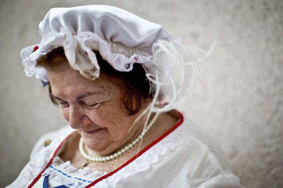 """Virginia """"Ginny"""" Evans bows her head in prayer during the Memorial Day Service at the Houston National Cemetery dressed in colonial era clothing, Monday, May 26, 2014, in Houston. Photo: Marie D. De Jesus, Houston Chronicle / © 2014 Houston Chronicle"""