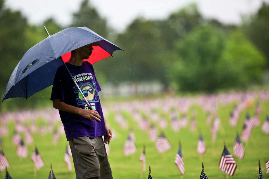 A man shields himself from the rain during a visit to the Houston National Cemetery after the Memorial Day Service, Monday, May 26, 2014, in Houston. Photo: Marie D. De Jesus, Houston Chronicle / © 2014 Houston Chronicle