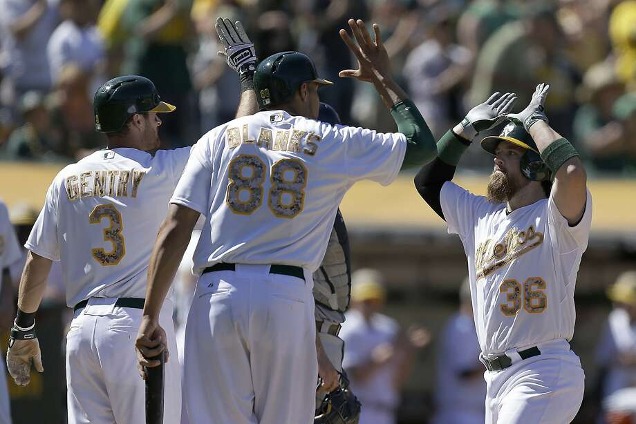 Oakland catcher Derek Norris (right) gets congratula- tions from Craig Gentry (left) and Kyle Blanks after his eighth-inning grand slam gave the A's a 10-0 lead over the Detroit Tigers on Memorial Day at  sold-out O.co Coliseum. Photo: Ben Margot, Associated Press