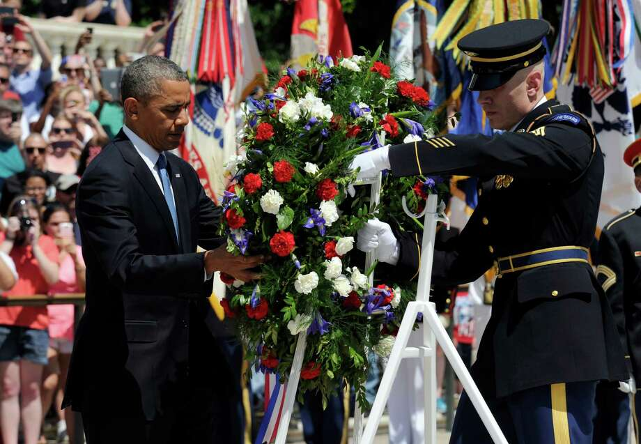 President Barack Obama lays a wreath at the Tomb of the Unknowns at Arlington National Cemetery in Arlington, Va., Monday, May 26, 2014.   President Obama is leading the nation in remembering its war heroes, the fallen and those still defending the flag, in a Memorial Day tribute.  (AP Photo/Susan Walsh) ORG XMIT: VASW101 Photo: Susan Walsh / AP