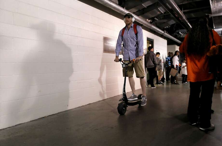 Giants' Hunter Pence rides his electric scooter away from the clubhouse after the San Francisco Giants beat the St. Louis Cardinals 6-1 in game six of the National League Championship Series, on Sunday Oct. 21, 2012 at AT&T Park, in  San Francisco, Calif. Photo: Michael Macor, The Chronicle