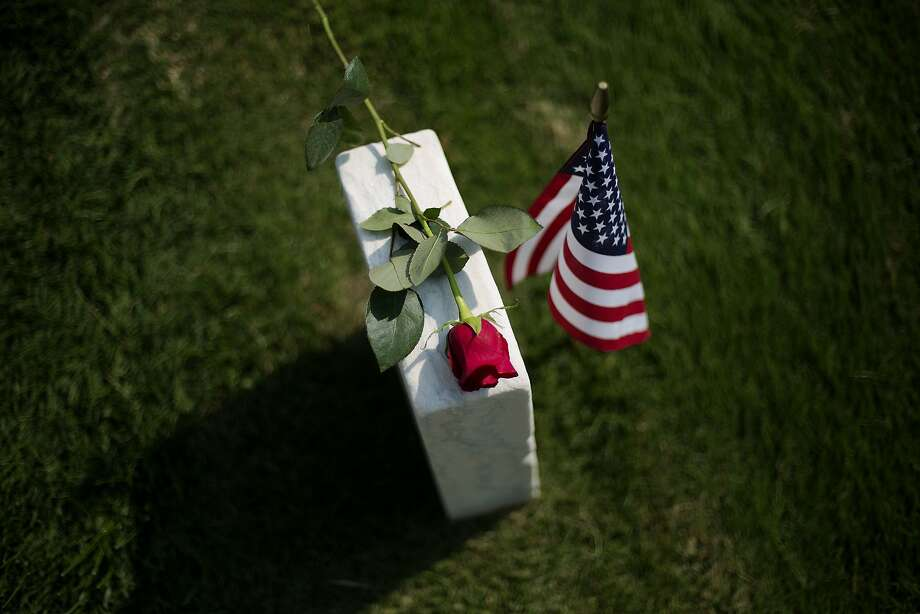 A rose sits on a tombstone of a civl war soldier at Marietta National Cemetery on Memorial Day, Monday, May 26, 2014, in Marietta, Ga. (AP Photo/David Goldman) Photo: David Goldman, Associated Press