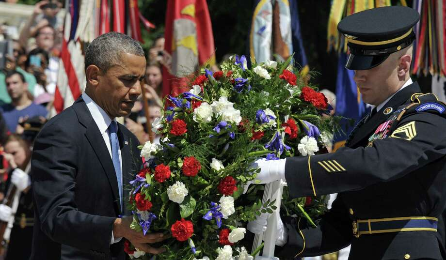 President Barack Obama lays a wreath at the Tomb of the Unknowns at Arlington National Cemetery on Monday. He also spoke to the crowd about the end of the war in Afghanistan. Photo: Susan Walsh / Associated Press / AP