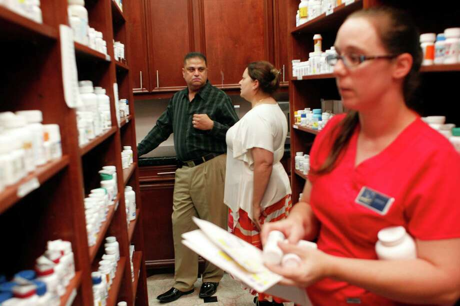 Milad and Maryana Attalla, owners of Katy Pharmacy, chat as employee Jessica Tisdale, right, looks for medicine to fill prescriptions. They've had the same employees since 2009. Photo: Johnny Hanson / © 2014  Houston Chronicle