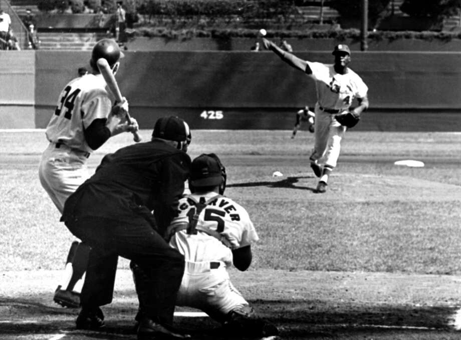 ST. LOUIS, MO - OCTOBER 15:  Pitcher Bob Gibson #45 of the St. Louis Cardinals throws the first pitch to Phil Linz #34 of the New York Yankees as catcher Tim McCarver #15 and umpire Frank Secory look on during Game 7 of the 1964 World Series on October 15, 1964 at Busch Stadium in St. Louis, Missouri. Photo: B Bennett, Getty Images / 1964 B Bennett