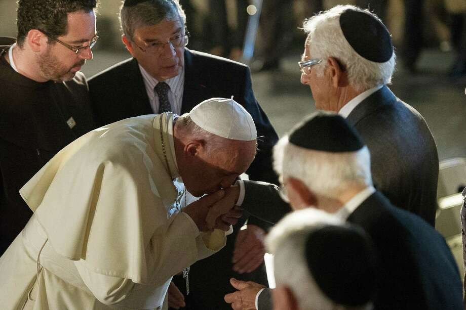 Pope Francis kisses a hand at a Holocaust museum in Jerusalem. In his Israeli visit, the pope walked a diplomatic tightrope with Muslims and Jews. Photo: L'Osservatore Romano Via The Associated Press / L'Osservatore Romano